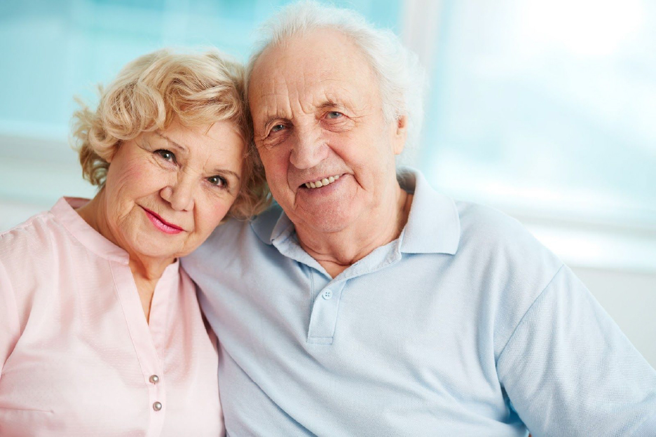 Elderly couple sitting together and smiling